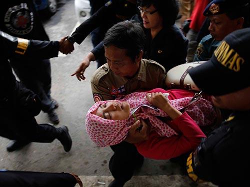 Một phụ nữ ngất xỉu sau khi hay tin tìm thấy thi thể nạn nhân đi trên chiếc máy bay mất tích Ảnh: REUTERS