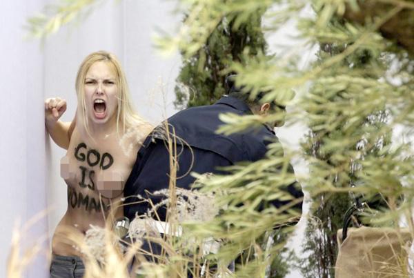 Trên ngực cô ta, được nhận dạng là  Inna Shevchenko, thủ lãnh nhóm Femen, ghi dòng chữ tiếng Anh: Chúa là đàn bà - Ảnh: AFP