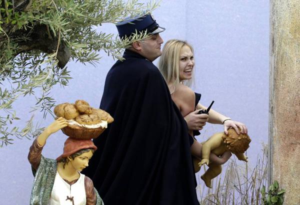 Cảnh sát Vatican khống chế người phụ nữ để ngực trần cướp tượng Chúa hài đồng ở Vatican ngày 25.12 - Ảnh: AFP