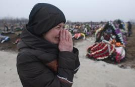Người thân của nạn nhân thiệt mạng do trúng pháo khóc thương tại một nghĩa trang ở thành phố cảng Mariupol, Ukraine, 27/1/2015