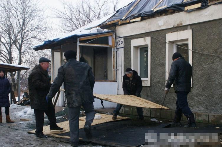 Những người đàn ông đang cố gắng sửa chữa lại căn nhà bị thiệt hại.