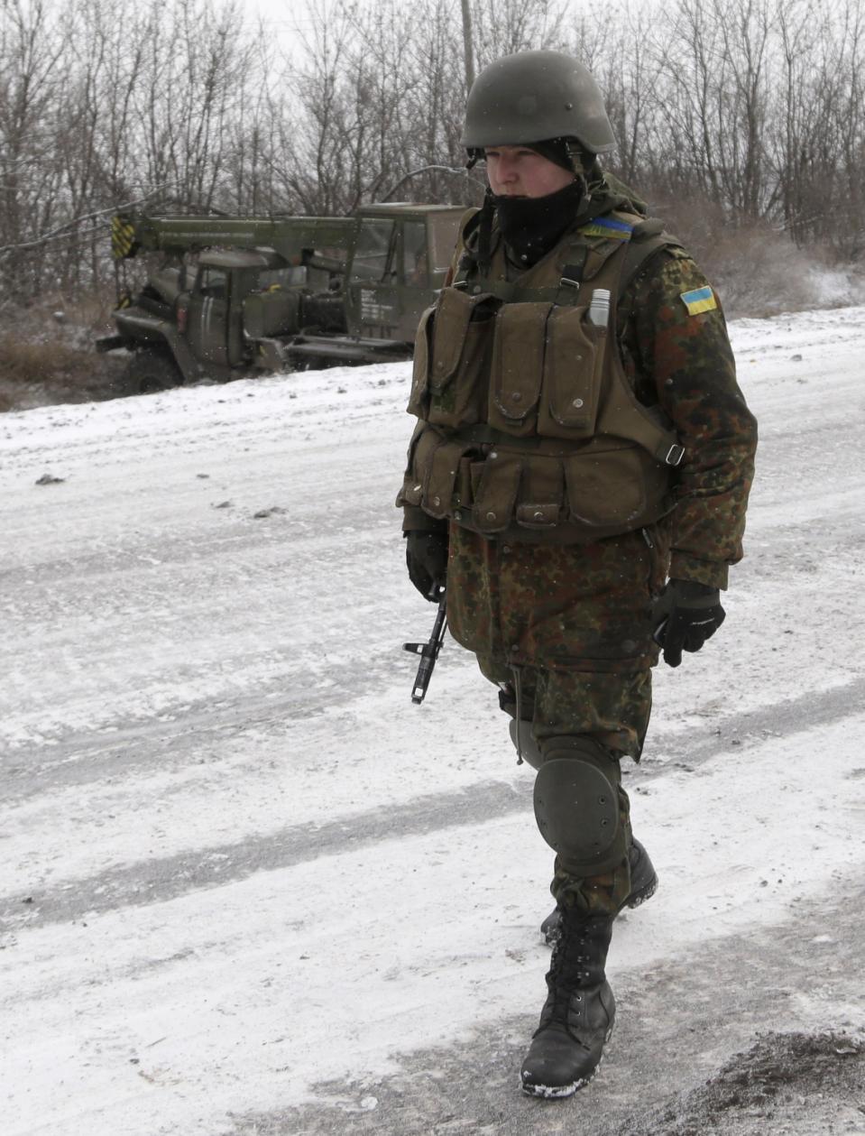 Một người lính Ukraine đi ngang qua chiếc xe tải chạy vào một con mương, gần đường giữa các thị trấn của Debaltseve và Artemivsk, Ukraine, Thứ hai 16 tháng 2, 2015