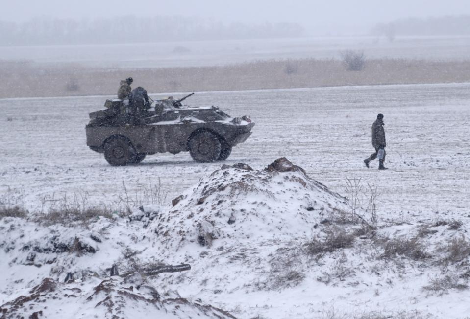 Một người lính Ukraine xách nước mang ra chiếc xe đang đỗ trên một cánh đồng gần đường giữa các thị trấn Debaltseve và Artemivsk, Ukraine, Thứ 2 16 Tháng 2, 2015.