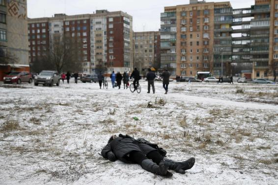The body of a woman killed by recent shelling lies on a street in the residential sector in the town of Kramatorsk