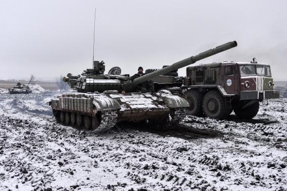 Ukrainian servicemen ride in a tank past a towing truck outside Debaltseve