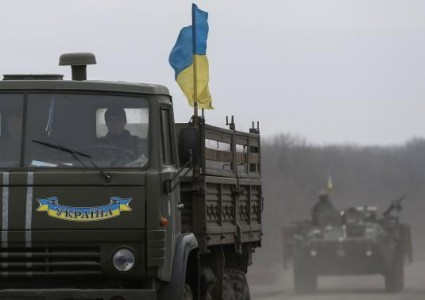 Members of the Ukrainian armed forces ride on military vehicles near Artemivsk