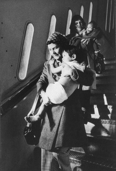 Hai phụ nữ bế trẻ em Việt Nam trong chương trình không vận khi máy bay hạ cánh tại Mỹ. Phần lớn trẻ em Babylift được đưa tới các gia đình có điều kiện tốt. Ảnh: AFP
