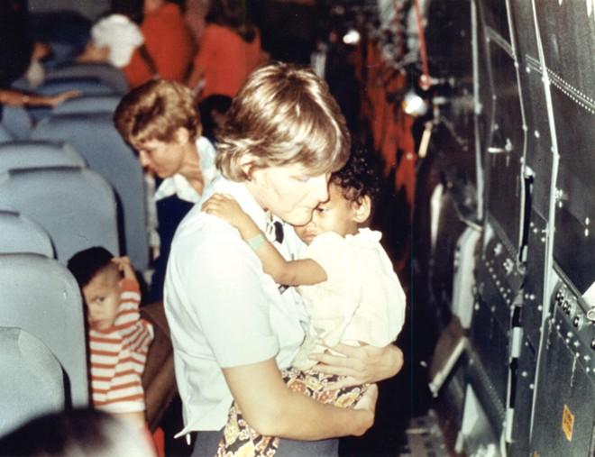 Một phụ nữ Mỹ vỗ về trẻ em trên chuyến bay rời khỏi Việt Nam. Sau đó, các em trở thành con nuôi trong các gia đình ở Mỹ, Canada, Australia và Pháp. Ảnh: DIA.mil