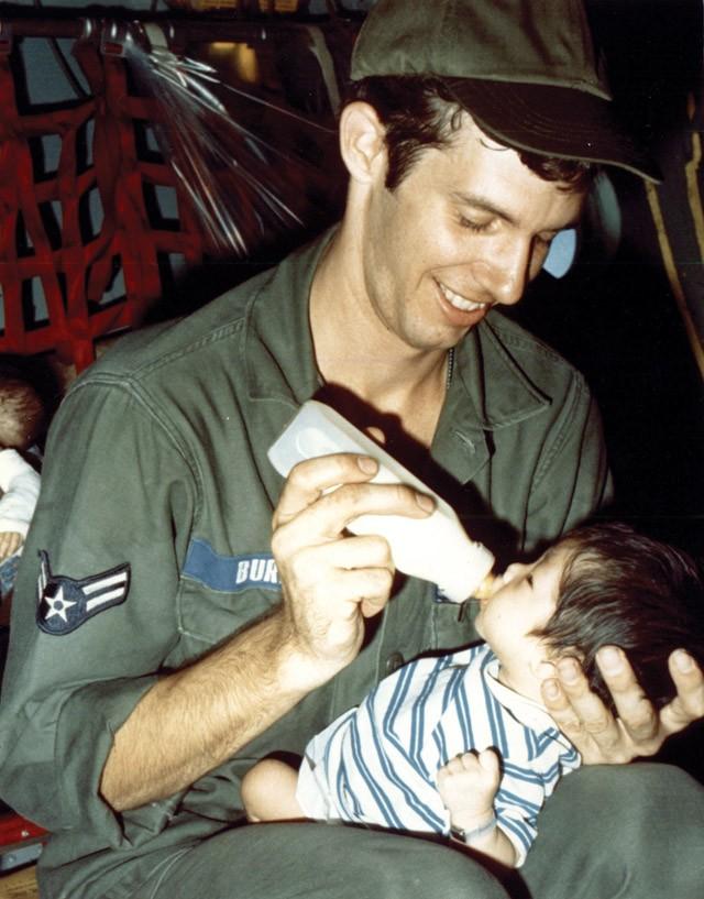 Một quân nhân Mỹ chăm sóc trẻ em Việt Nam trong chuyến bay rời Sài Gòn. Sau này, chương trình Babylift trở thành chủ đề tranh cãi và chỉ trích từ chính dư luận Mỹ. Ảnh: DIA.mil