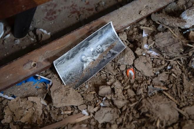 Đồ vật vương vãi trên sàn nhà, bị vùi trong đống đổ nát.