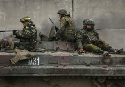 Members of the Ukrainian armed forces ride on an armoured personnel carrier near Artemivsk