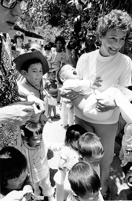 Các tình nguyện viên Mỹ đưa trẻ em mồ côi lên xe buýt ở Sài Gòn ngày 11/4/1975. Sau đó, một máy bay không quân Mỹ chở các em sang nước này làm con nuôi cho các gia đình.