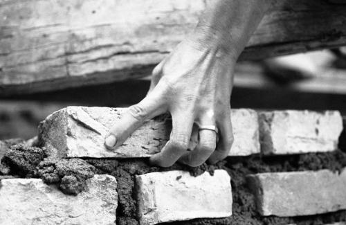 Bàn tay một phụ nữ ở Chợ Lớn, tự đặt từng viên gạch, trát từng mạch vữa trong nỗ lực dựng lại ngôi nhà của mình đã bị tàn phá trong các cuộc tấn công, tháng 8/1968. (AP/ The Atlantic)