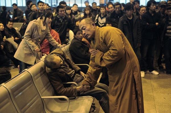 Một nhà sư đang cầu nguyện cho một người đàn ông đột tử bất ngờ khi đang đợi tàu ở nhà ga. Ảnh chụp tại Trung Quốc.
