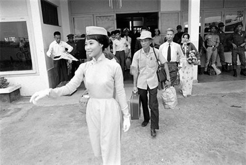 Nữ tiếp viên Hàng không của Sài Gòn thập niên 70 với phong thái chuyên nghiệp trong áo dài thắt eo cao, mũ và găng tay đồng bộ.