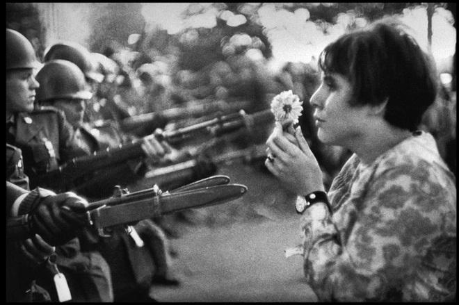 """Jan Rose Kasmir, vào thời điểm đó là học sinh cấp ba, tham gia cuộc diễu hành đến Lầu Năm Góc để phản đối chiến tranh Việt Nam tháng 10/1967. Hình ảnh cô cầm hoa đứng trước hàng cảnh vệ được nhiếp ảnh gia người Pháp Marc Riboud ghi lại đã trở thành biểu tượng của phong trào phản chiến. """"Cô ấy chỉ nói chuyện, cố gắng thu hút sự chú ý của những người lính, có thể là đang cố gắng trò chuyện cùng họ"""", Riboud nói trong một cuộc phỏng vấn năm 2004. """"Tôi có cảm giác là những người lính còn sợ cố ấy hơn cô ấy sợ những lưỡi lê""""."""