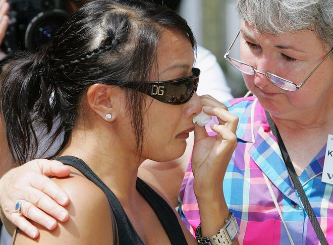 Cô gái mồ côi Lyly Kara Koenig, một thành viên của đoàn, rơi nước mắt khi thăm một trại trẻ và được mẹ nuôi an ủi.