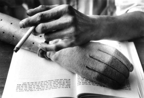 Một người Việt đọc sách, hút thuốc bên cánh tay giả, tháng 8/1968. (AP/ The Atlantic)