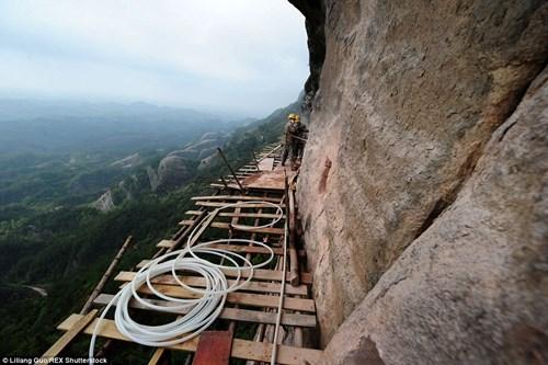 Giàn giáo bằng gỗ rộng hơn 3m, cheo leo trên vách núi