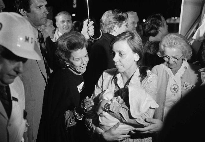 Đệ nhất Phu nhân Mỹ Betty Ford chào đón một trong những em bé được tình nguyện viên y tế đưa lên xe buýt quân đội, tại sân bay San Francisco ngày 5/4. Khi đó, một máy bay của hãng Pan Am Airlines chở 325 trẻ mồ côi từ Việt Nam vừa hạ cánh.