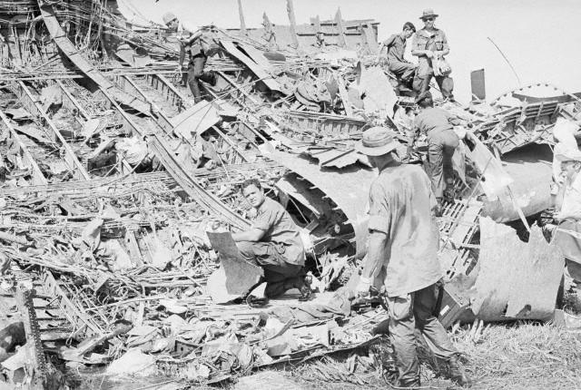 Các quan chức quân sự Mỹ tìm nạn nhân giữa những mảnh vỡ phi cơ. Ảnh: AFP