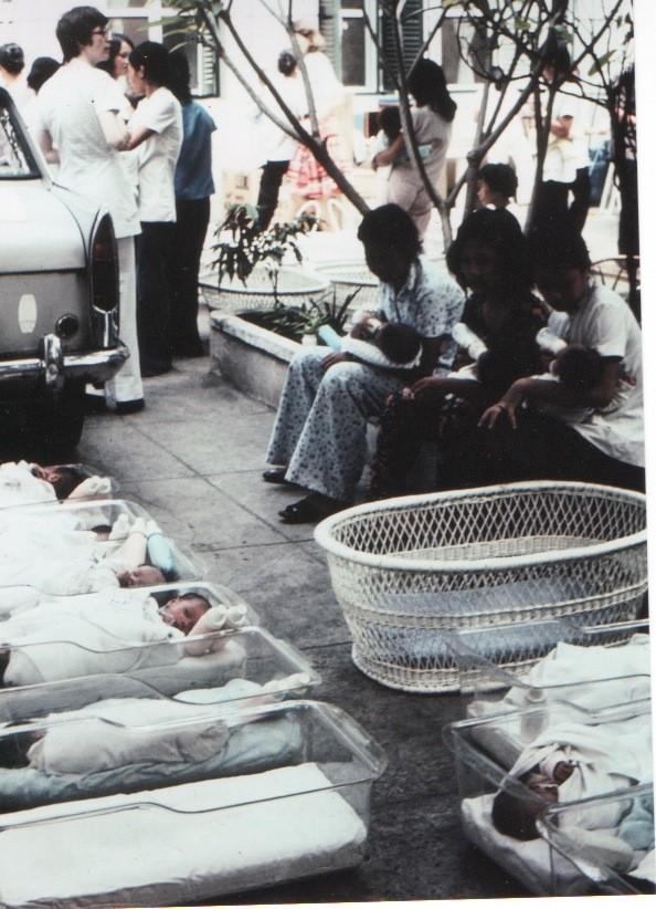 Xơ Susan (áo trắng, trái) đặt trẻ mồ côi vào lồng nhựa để chuẩn bị đưa lên máy bay.