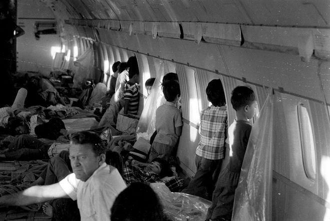 Những đứa trẻ trên chuyến bay đầu tiên rời khỏi Sài Gòn nhìn ra bên ngoài qua cửa sổ của máy bay DC 8 thuộc hãng hàng không World Airways. Ước tính 3.000 trẻ em, trong đó có 150 em sống sót sau vụ tai nạn máy bay C-5, đã rời khỏi miền Nam Việt Nam từ ngày 2 đến 29/4/1975.