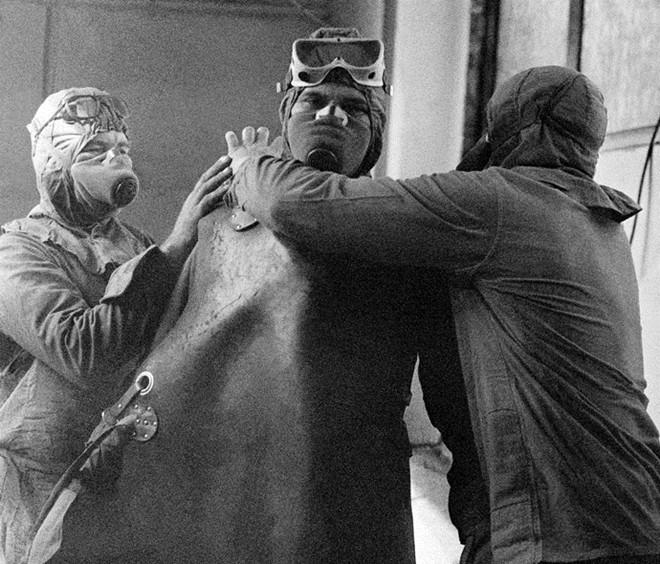 Nhân viên tham gia quá trình khắc phục hậu quả thảm họa phải đeo mặt nạ chống độc. Ảnh: RIA Novosti
