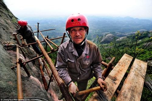 Một công nhân đang cố gắng gắn các thanh gỗ vào vách núi để mở đường