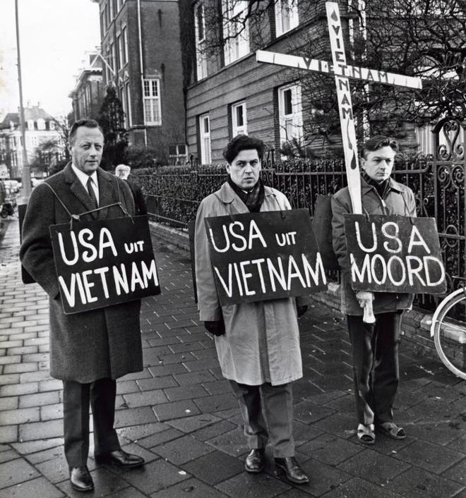 """Ba người đàn ông đeo biển """"Mỹ, hãy ra khỏi Việt Nam"""" đứng trước Lãnh sự quán Mỹ tại The Hauge, Hà Lan năm 1967. Ảnh: Nationalarchivebot"""