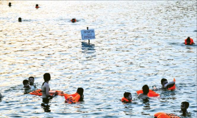 Hồ Linh Đàm (Hà Nội) đang bị ô nhiễm nghiêm trọng nhưng cũng thành bể bơi giải nhiệt ngày nắng nóng - Ảnh: Quang Thế