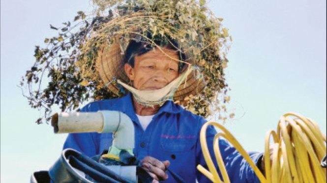 Nắng nóng như đổ lửa, ông Hồ Viết Cang (thôn Nam Hà 1, xã Điện Trung, huyện Điện Bàn, Quảng Nam) dùng cỏ dại kết vào chiếc nón cho bớt nóng - Ảnh: Lê Trung