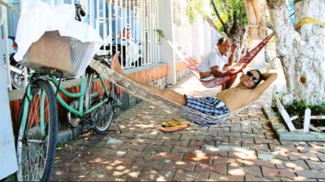 Không chịu được cái nóng khủng khiếp của miền Trung, nhiều cụ già mang theo võng ra vỉa hè đường Bạch Đằng, dọc bờ sông Hàn (TP Đà Nẵng) để ngủ trưa - Ảnh: Phan Thành