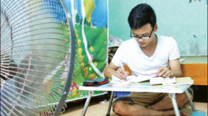 Phạm Thái Huy, sinh viên Trường ĐH Hải Phòng, chống nắng nóng bằng cách dùng chậu nước mát đặt trước quạt khi ở trong phòng trọ cấp 4 của mình - Ảnh: Tiến Thắng