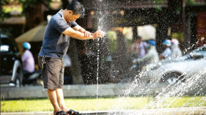 Giữa trưa hè, một người đàn ông nhờ đến vòi phun nước công cộng trên phố Quán Thánh (Hà Nội) để làm mát cơ thể - Ảnh: Nguyễn Khánh