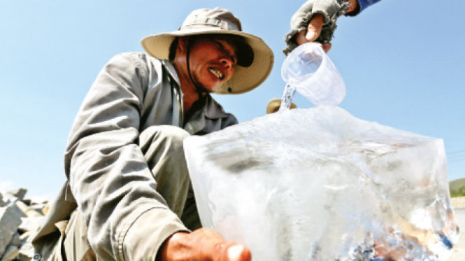 Ông Đỗ Văn Rừng dùng cả tảng đá cây làm chậu đổ nước vào cho mau lạnh để giải khát cho anh em công nhân trên quốc lộ 1 đoạn qua xã Ninh Lộc, Khánh Hòa - Ảnh: Tiến Thành
