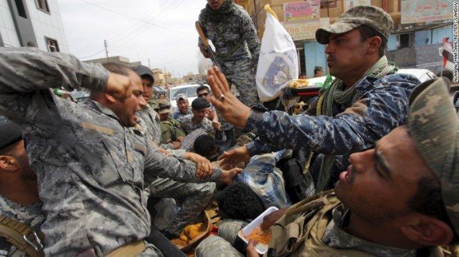 Một người lính Iraq đánh một kẻ bị tình nghi là quân của IS - Ảnh: CNN