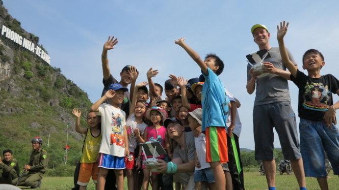 Trẻ em Quảng Bình thích thú theo dõi hai chuyên gia của ABC kiểm tra thiết bị quay phim từ xa (flycam) - Ảnh: Lê Nam
