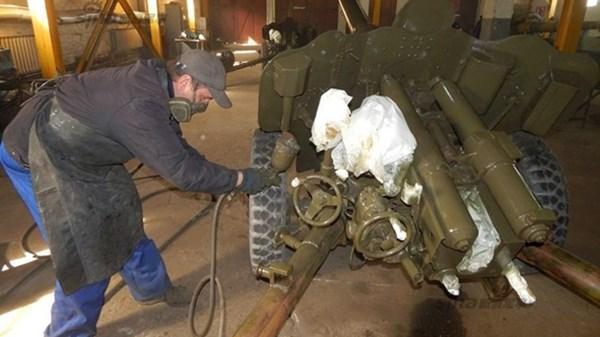 Một nhân viên nhà máy đang sơn phủ khẩu pháo sau khi đã được sửa chữa xong.