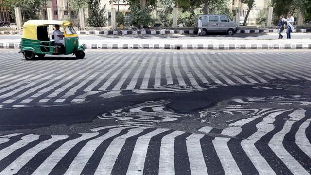 Nhựa đường chảy ra dưới sức nóng kinh người - Ảnh: EPA