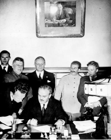 Ngoại trưởng Vyacheslav Molotov trong lễ ký Hiệp ước  Ribbentrop-Molotov dưới sự chứng kiến của Stalin (Moscow Times)