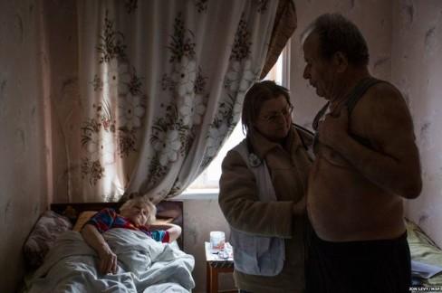 Bác sĩ Svetlana Niekurasa, người đã lựa chọn ở lại thị trấn trong cuộc xung đột, đang kiểm tra sức khỏe cho ông Ivan Vorobyeva, 74 tuổi. Ông đang một mình chăm sóc người vợ ốm yếu tại nhà riêng trong  Debaltseve