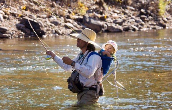 """Cha """"địu"""" theo cậu bé trên lưng trong một chuyến đi câu cá tại sông Dolores thuộc bang Colorado, Mỹ - Ảnh: BILL HATCHER/NG"""