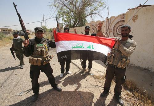 Lực lượng dân quân dòng Shiite giơ cao quốc kỳ Iraq sau khi giành lại quyền kiểm soát thành phố Baiji từ IS.