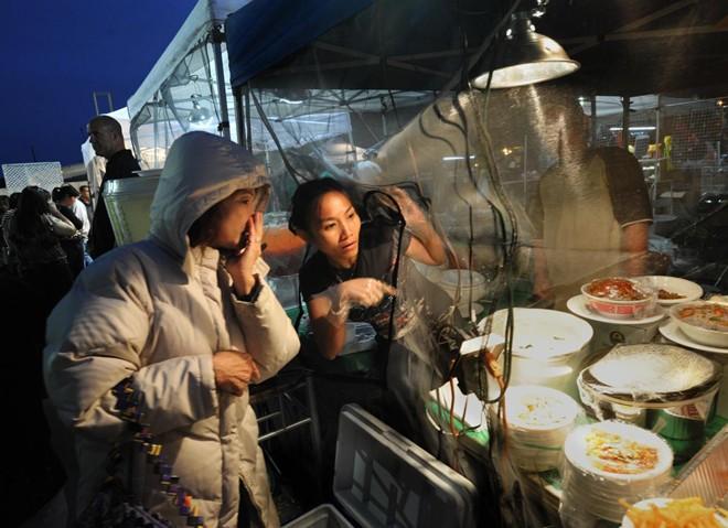Quầy bán thức ăn của cô Nhung Nguyen. Chợ sẽ hoạt động vào mỗi buổi tối trong mùa hè với 18 quầy bán đồ ăn và khoảng 25 gian bán các vật phẩm khác.