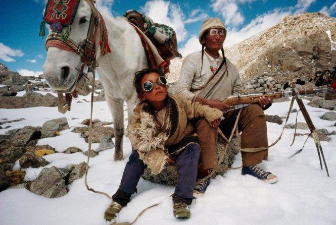 Cha và con trai ngồi cạnh nhau nghỉ ngơi bên chú ngựa trong cuộc hành hương qua núi Kailas thuộc Tây Tạng - Ảnh: LYNN JOHNSON/NG
