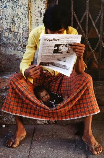Đứa trẻ nằm bên trên chiếc váy truyền thống longyi (của đàn ông Myanmar) trong lúc người cha đang ngồi đọc báo. Đây là bức ảnh xuất hiện trong tạp chí của National Geographic trong số ra tháng 5-1984 - Ảnh: JAMES L. STANFIELD/NG
