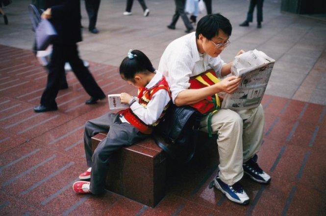 Cha và con gái mải mê đọc báo tại khu vực băng ghế đá đường Nanjing, Thượng Hải, Trung Quốc - Ảnh: XPACIFICA/NG