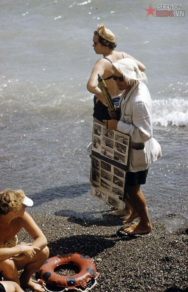 Một người thợ chụp ảnh tìm kiếm khách hàng trên bãi biển.