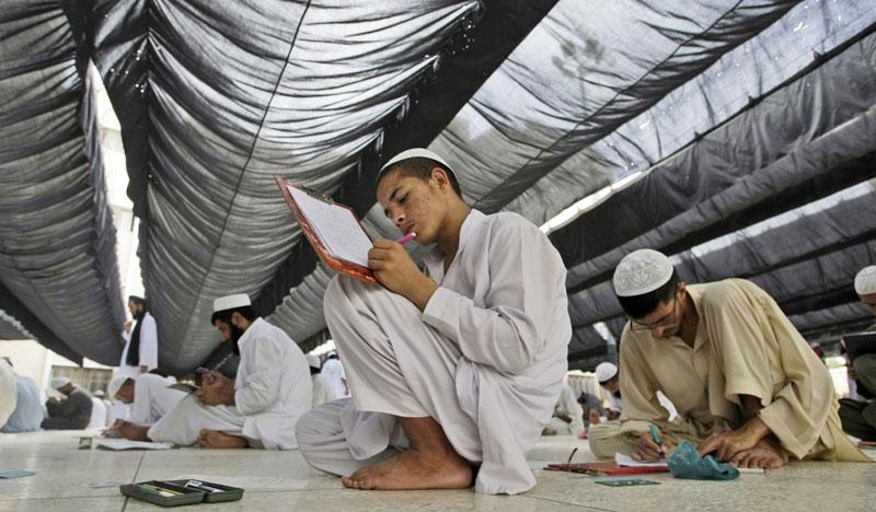 Học sinh Pakistan ngồi trên sàn làm bài thi tại Chủng viện Hồi giáo Jamia Binoria ở Karachi, Pakistan ngày 8/6/2013. Binoria là một trong những chủng viện mẫu, đã sửa đổi giáo trình giảng dạy của mình bằng việc bổ sung các môn học như máy vi tính, toán học và khoa học. Ảnh: AP